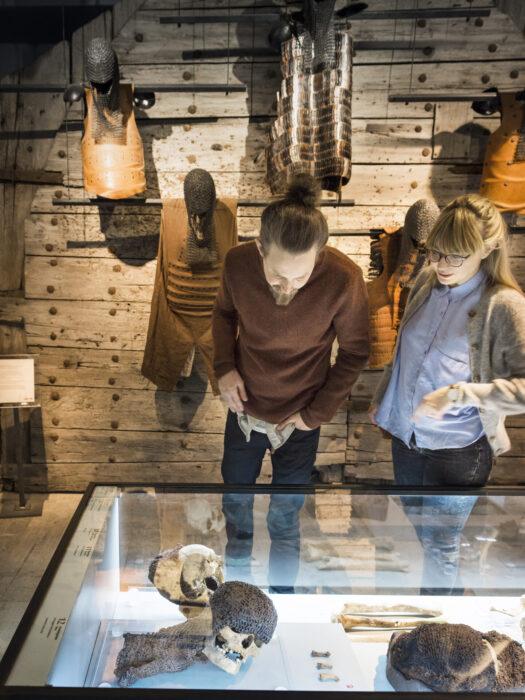 Ett par tittar ner i en monter i utställningen 1361-slaget om Gotland