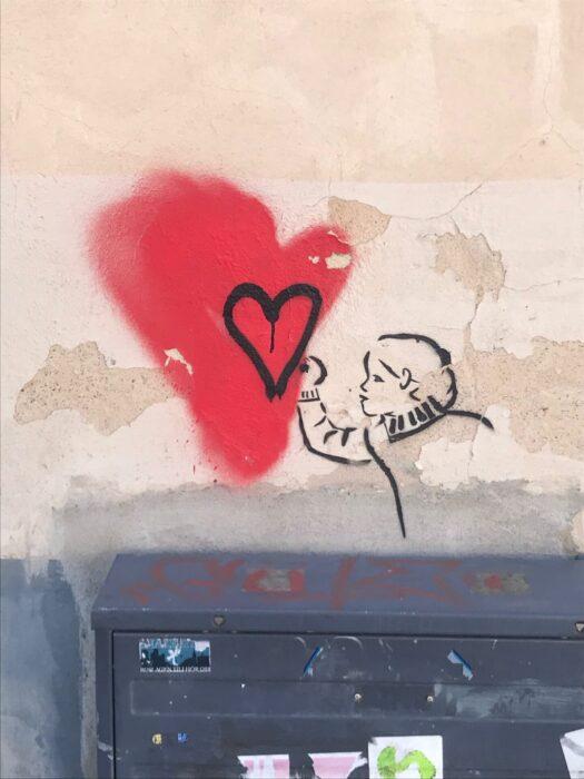 Målning på vägg föreställande ett hjärta och en person