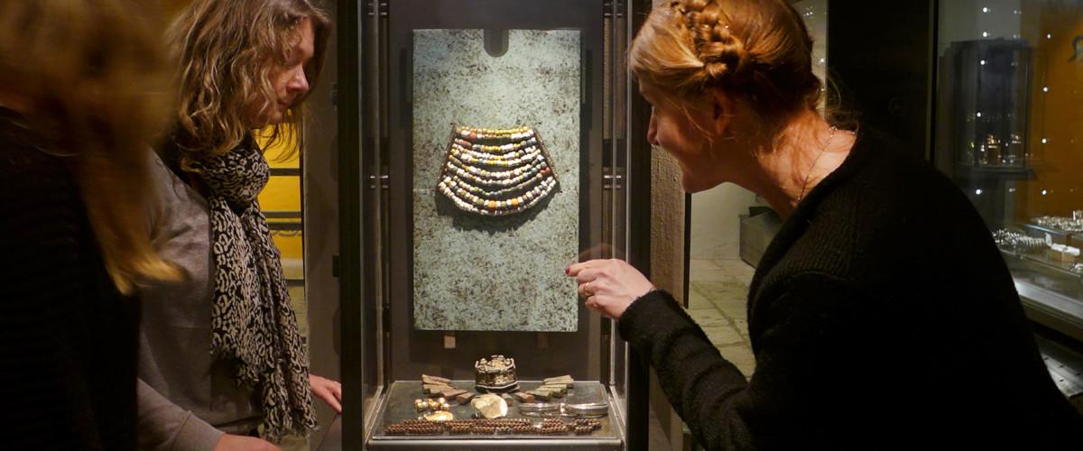 Kvinna pekar in i monter med föremål.